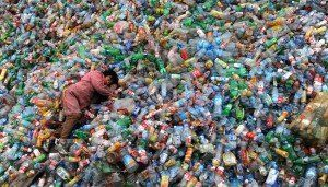 Trabajador descansando sobre montaña de plástico.